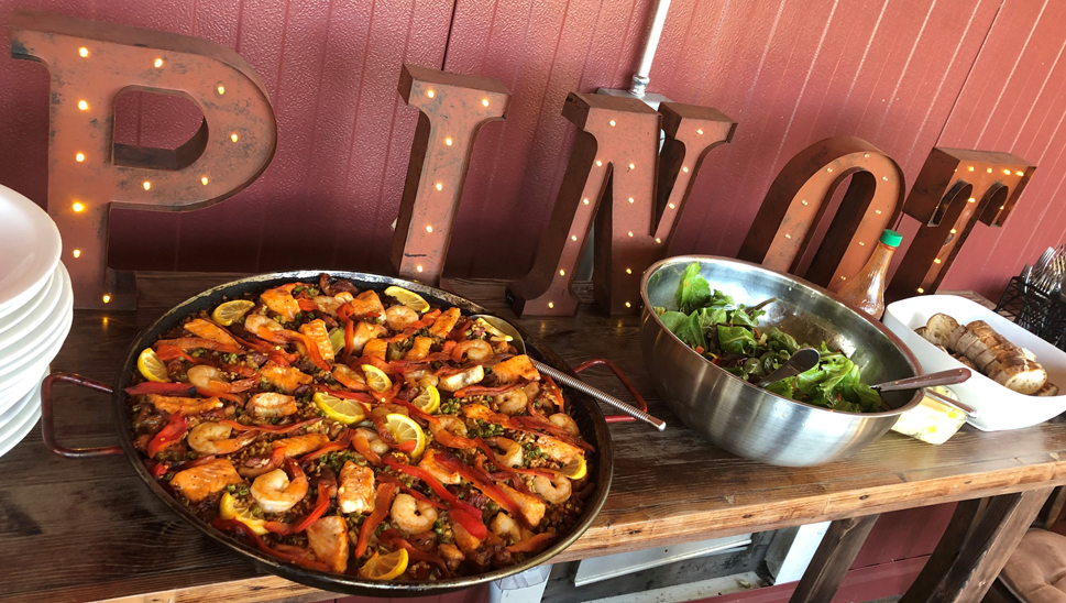 a pan of paella and a green salad with a Pinot sign behind