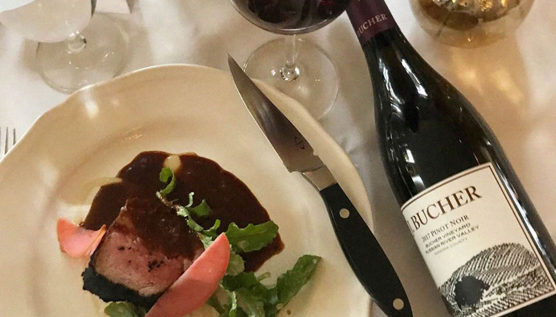 A photo of a fine steak and Pinot Noir dining experience at a Bucher winemaker dinner