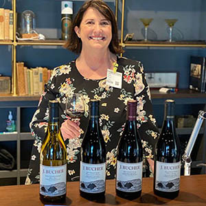 Diane Bucher at a counter pouring tastes of Bucher pinots and chardonnays