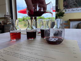 Individual carafes filled with ACORN wines and an ACORN logo GoVino glass for visiting tasters