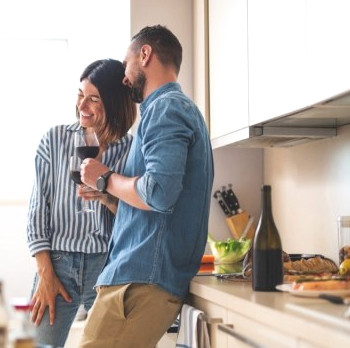 Couple enjoying wine in kitchen